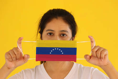 A woman in white shirt with Venezuela flag on hygienic mask in her hand and lifted up the front face on yellow background. Tiny Particle or virus corona or Covid 19 protection. Concept of Combating illness.