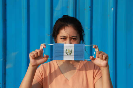 A woman with Guatemala flag on hygienic mask in her hand and lifted up the front face on blue background. Tiny Particle or virus corona or Covid 19 protection. Concept of Combating illness.