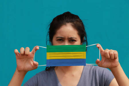 A woman with Gabon flag on hygienic mask in her hand and lifted up the front face on light blue color background. Tiny Particle or virus corona or Covid 19 protection. Concept of Combating illness. 版權商用圖片