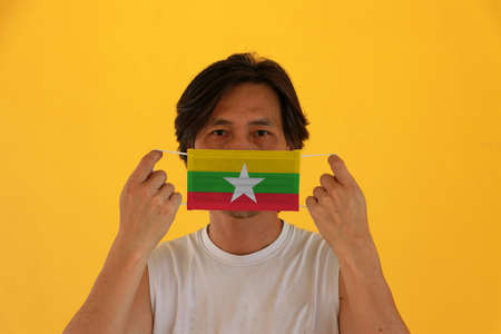 A man with Myanmar flag on hygienic mask in his hand and lifted up the front face on yellow background. Tiny Particle or virus corona or Covid 19 protection. Concept of Combating illness. 版權商用圖片