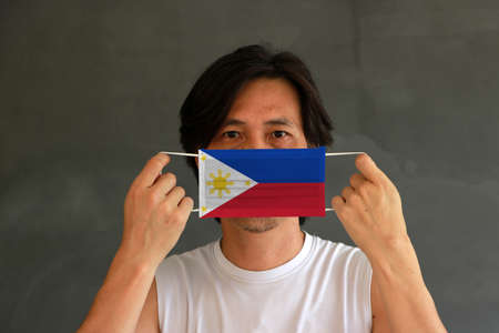 A man with Philippines flag on hygienic mask in his hand and lifted up the front face on dark grey background. Tiny Particle or virus corona or Covid 19 protection. Concept of Combating illness.