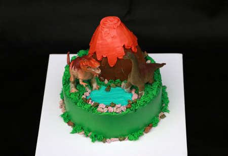 Two dinosaur dolls decorate on a volcanic cake and green forest place on a white square plate on black background.