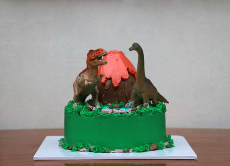 Two dinosaur dolls decorate on a volcanic cake and green forest place on a white square plate on wooden floor. 版權商用圖片
