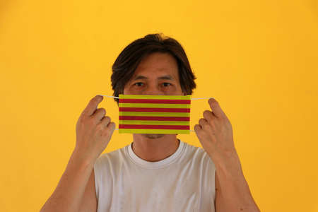 A man with Catalunya flag on hygienic mask in his hand and lifted up the front face on yellow background. Tiny Particle or virus corona or Covid 19 protection. Concept of Combating illness. 版權商用圖片