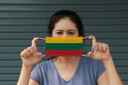 A woman with Lithuania flag on hygienic mask in her hand and lifted up the front face on dark green background. Tiny Particle or virus corona or Covid 19 protection. Concept of Combating illness.