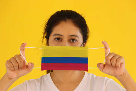 A woman in white shirt with Colombia flag on hygienic mask in her hand and lifted up the front face on yellow background. Tiny Particle or virus corona or Covid 19 protection. Concept of Combating illness. 版權商用圖片