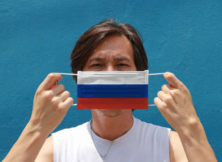 A man with Russia flag on hygienic mask in his hand and lifted up the front face on blue background. Tiny Particle or virus corona or Covid 19 protection. Concept of Combating illness.