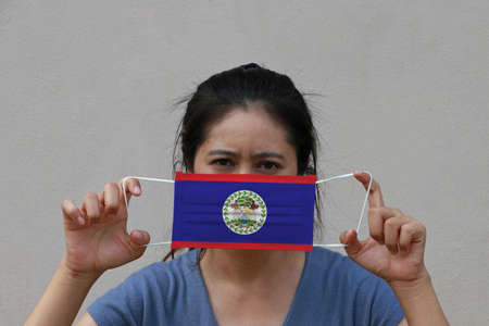 A woman with Belize flag on hygienic mask in her hand and lifted up the front face on beige color background. Tiny Particle or virus corona or Covid 19 protection. Concept of Combating illness.