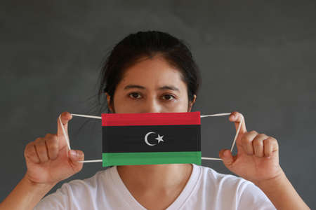 A woman in white shirt with Libya flag on hygienic mask in her hand and lifted up the front face on dark grey background. Tiny Particle or virus corona or Covid 19 protection. Concept of Combating illness.