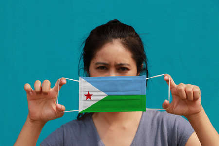 A woman with Djibouti flag on hygienic mask in her hand and lifted up the front face on light blue color background. Tiny Particle or virus corona or Covid 19 protection. Concept of Combating illness. 版權商用圖片
