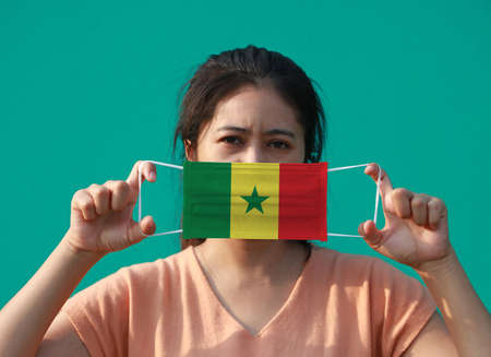 A woman with Senegal flag on hygienic mask in her hand and lifted up the front face on green background. Tiny Particle or virus corona or Covid 19 protection. Concept of Combating illness.