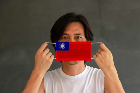 A man with Taiwan flag on hygienic mask in his hand and lifted up the front face on dark grey background. Tiny Particle or virus corona or Covid 19 protection. Concept of Combating illness.