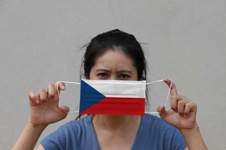 A woman with Czech Republic flag on hygienic mask in her hand and lifted up the front face on beige color background. Tiny Particle or virus corona or Covid 19 protection. Concept of Combating illness. 版權商用圖片