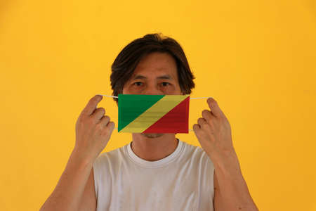 A man with Congo flag on hygienic mask in his hand and lifted up the front face on yellow background. Tiny Particle or virus corona or Covid 19 protection. Concept of Combating illness. 版權商用圖片