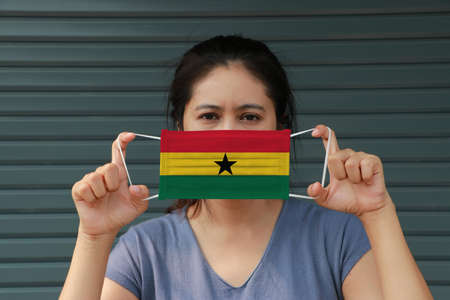 A woman with Ghana flag on hygienic mask in her hand and lifted up the front face on dark green background. Tiny Particle or virus corona or Covid 19 protection. Concept of Combating illness. 版權商用圖片