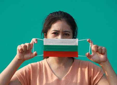 A woman with Bulgaria flag on hygienic mask in her hand and lifted up the front face on green background. Tiny Particle or virus corona or Covid 19 protection. Concept of Combating illness.