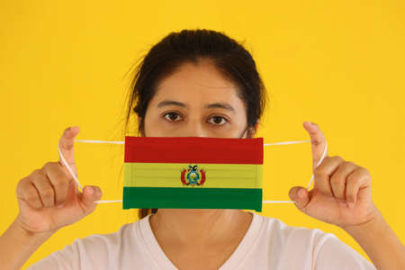 A woman in white shirt with Bolivia flag on hygienic mask in her hand and lifted up the front face on yellow background. Tiny Particle or virus corona or Covid 19 protection. Concept of Combating illness.