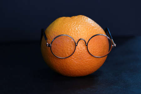 Oranges which are fruit, wear glasses on black background.