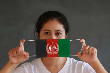 A woman in white shirt with Afghanistan flag on hygienic mask in her hand and lifted up the front face on dark grey background. Tiny Particle or virus corona or Covid 19 protection. Concept of Combating illness.