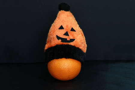 Oranges which are fruit, wear orange color of halloween hat on black background.