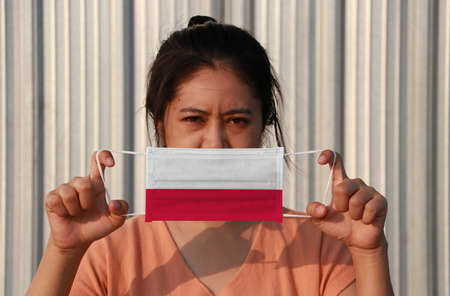 A woman with Poland flag on hygienic mask in her hand and lifted up the front face on grey background. Tiny Particle or virus corona or Covid 19 protection. Concept of Combating illness.