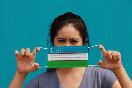 A woman with Uzbekistan flag on hygienic mask in her hand and lifted up the front face on light blue color background. Tiny Particle or virus corona or Covid 19 protection. Concept of Combating illness. 版權商用圖片