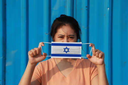 A woman with Israel flag on hygienic mask in her hand and lifted up the front face on blue background. Tiny Particle or virus corona or Covid 19 protection. Concept of Combating illness. 版權商用圖片