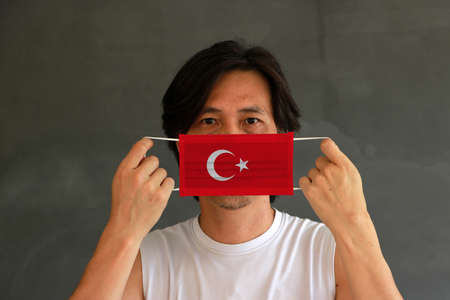 A man with Turkey flag on hygienic mask in his hand and lifted up the front face on dark grey background. Tiny Particle or virus corona or Covid 19 protection. Concept of Combating illness.