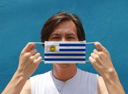 A man with Uruguay flag on hygienic mask in his hand and lifted up the front face on blue background. Tiny Particle or virus corona or Covid 19 protection. Concept of Combating illness. 版權商用圖片