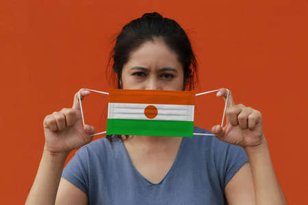 A woman with Niger flag on hygienic mask in her hand and lifted up the front face on orange color background. Tiny Particle or virus corona or Covid 19 protection. Concept of Combating illness. 版權商用圖片