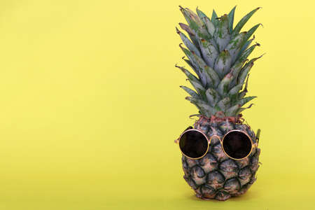 Pineapple wearing sunglasses on yellow background.