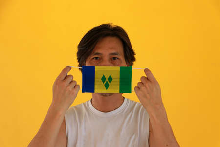 A man with Saint Vincent and the Grenadines flag on hygienic mask in his hand and lifted up the front face on yellow background. Tiny Particle or virus corona or Covid 19 protection. Concept of Combating illness.
