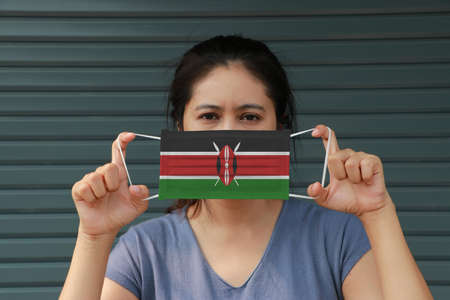 A woman in white shirt with Kenya flag on hygienic mask in her hand and lifted up the front face on dark grey background. Tiny Particle or virus corona or Covid 19 protection. Concept of Combating illness. 版權商用圖片