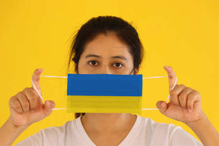 A woman in white shirt with Ukraine flag on hygienic mask in her hand and lifted up the front face on yellow background. Tiny Particle or virus corona or Covid 19 protection. Concept of Combating illness. 版權商用圖片