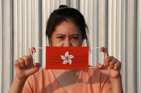 A woman with Hong Kong flag on hygienic mask in her hand and lifted up the front face on grey background. Tiny Particle or virus corona or Covid 19 protection. Concept of Combating illness.