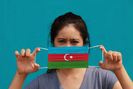 A woman with Azerbaijan flag on hygienic mask in her hand and lifted up the front face on light blue color background. Tiny Particle or virus corona or Covid 19 protection. Concept of Combating illness.
