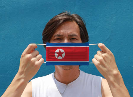 A man with North Korea flag on hygienic mask in his hand and lifted up the front face on blue background. Tiny Particle or virus corona or Covid 19 protection. Concept of Combating illness.