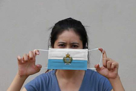 A woman with San Marino flag on hygienic mask in her hand and lifted up the front face on beige color background. Tiny Particle or virus corona or Covid 19 protection. Concept of Combating illness.