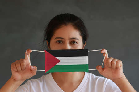 A woman in white shirt with Palestine flag on hygienic mask in her hand and lifted up the front face on dark grey background. Tiny Particle or virus corona or Covid 19 protection. Concept of Combating illness.