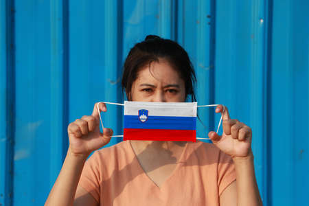 A woman with Slovenia flag on hygienic mask in her hand and lifted up the front face on blue background. Tiny Particle or virus corona or Covid 19 protection. Concept of Combating illness.