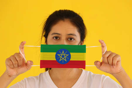 A woman in white shirt with Ethiopia flag on hygienic mask in her hand and lifted up the front face on yellow background. Tiny Particle or virus corona or Covid 19 protection. Concept of Combating illness.
