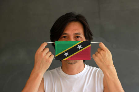 A man with Saint Kitts and Nevis flag on hygienic mask in his hand and lifted up the front face on dark grey background. Tiny Particle or virus corona or Covid 19 protection. Concept of Combating illness.