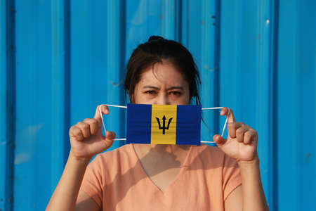 A woman with Barbados flag on hygienic mask in her hand and lifted up the front face on blue background. Tiny Particle or virus corona or Covid 19 protection. Concept of Combating illness. Foto de archivo