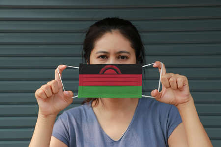 A woman with Malawi flag on hygienic mask in her hand and lifted up the front face on dark green background. Tiny Particle or virus corona or Covid 19 protection. Concept of Combating illness.