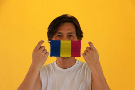 A man with Chad flag on hygienic mask in his hand and lifted up the front face on yellow background. Tiny Particle or virus corona or Covid 19 protection. Concept of Combating illness.