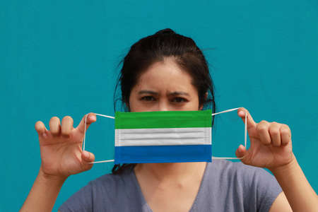 A woman with Sierra leone flag on hygienic mask in her hand and lifted up the front face on light blue color background. Tiny Particle or virus corona or Covid 19 protection. Concept of Combating illness.