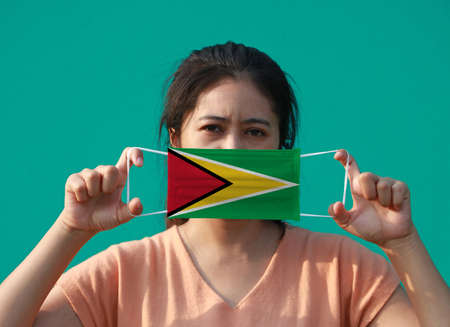 A woman with Guyana flag on hygienic mask in her hand and lifted up the front face on green background. Tiny Particle or virus corona or Covid 19 protection. Concept of Combating illness.