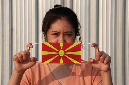 A woman with Macedonia flag on hygienic mask in her hand and lifted up the front face on grey background. Tiny Particle or virus corona or Covid 19 protection. Concept of Combating illness.