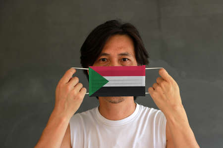 A man with Sudan flag on hygienic mask in his hand and lifted up the front face on dark grey background. Tiny Particle or virus corona or Covid 19 protection. Concept of Combating illness. Archivio Fotografico - 157449754