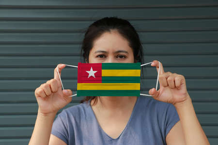 A woman with Togo flag on hygienic mask in her hand and lifted up the front face on dark green background. Tiny Particle or virus corona or Covid 19 protection. Concept of Combating illness. Archivio Fotografico - 157449755
